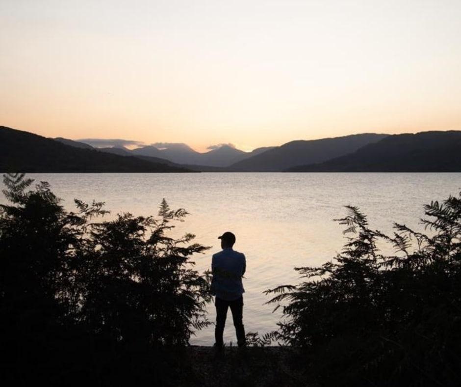 man standing overlooking the water